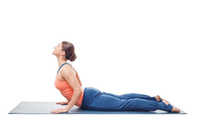 Beautiful sporty fit yogini woman practices yoga asana bhujangasana - cobra pose in studio isolated on white