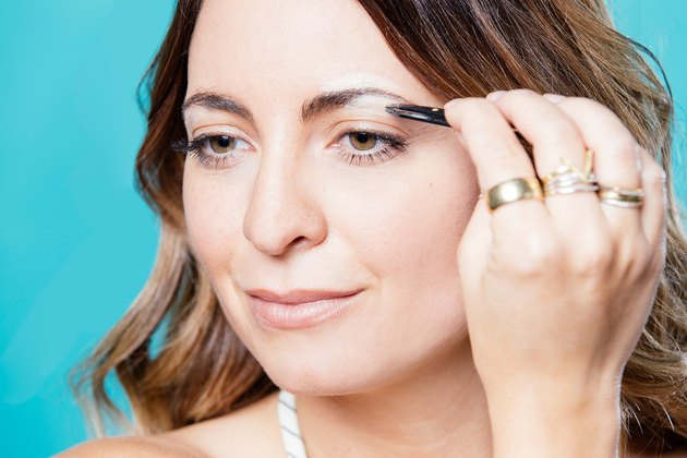 Jenna Gruttadauria plucks her brow with tweezers