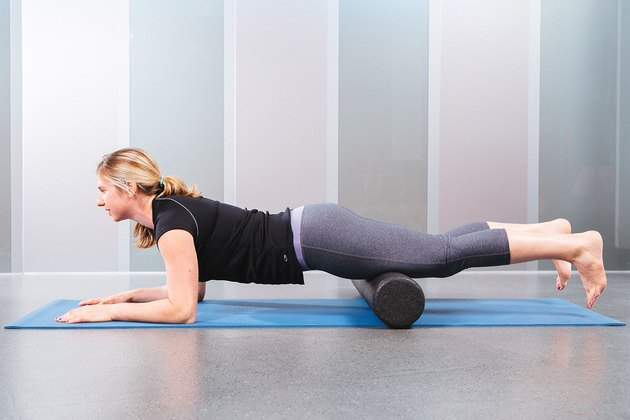 woman using foam roller on an exercise mat