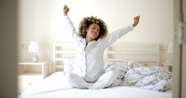 A woman in pajamas stretching before she gets out of bed