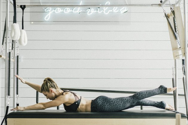 Woman performing swimming pilates exercise.