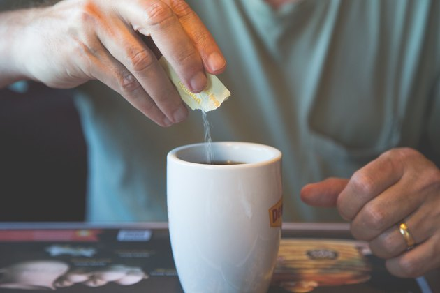 man pouring sugar substitute into coffee