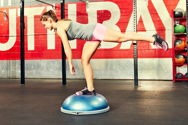 Woman performing single-leg romanian deadlift BOSU ball exercise