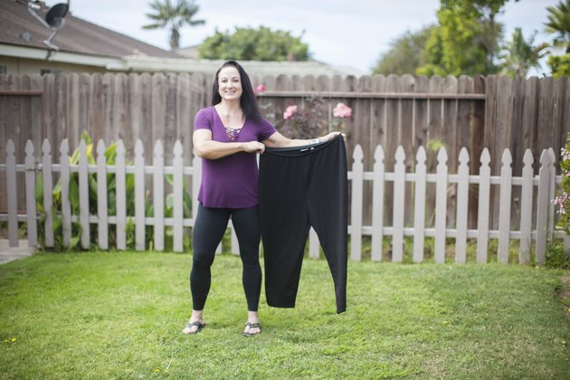 Stacy holds a pair of her pants from before her weight loss.