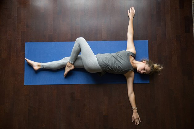 Attractive young woman working out indoors, doing yoga exercise on wooden floor, lying in Reclining Spinal Twist, Jathara Parivartanasana, resting after practice, full length, top view