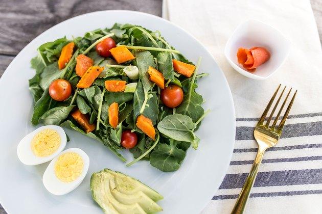 plate with salad, hard-boiled egg, avocado and smoked salmon