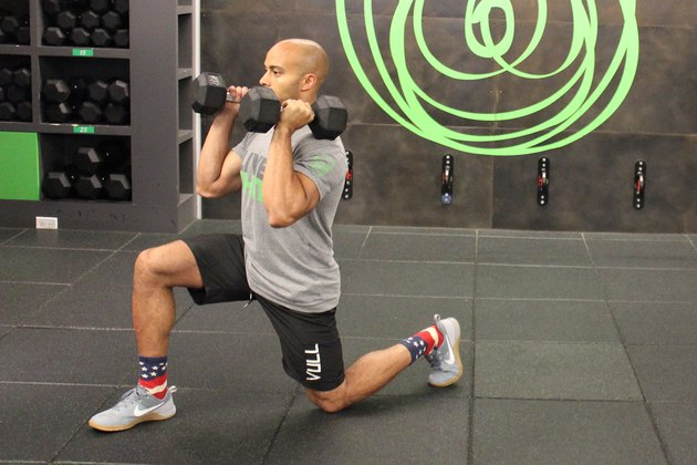 Man doing a dumbbell forward lunge during a 17-minute HIIT workout