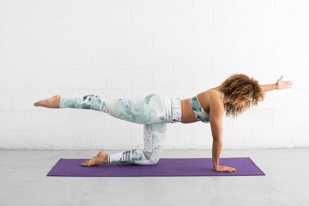 woman does bird dog ab exercise on a yoga mat