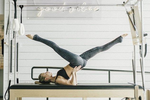 Pilates instructor performing scissor exercise on a Pilates reformer machine.
