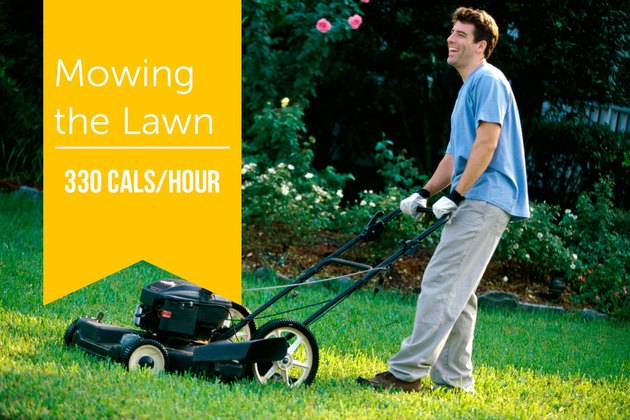 Side profile of a mid adult man mowing the lawn