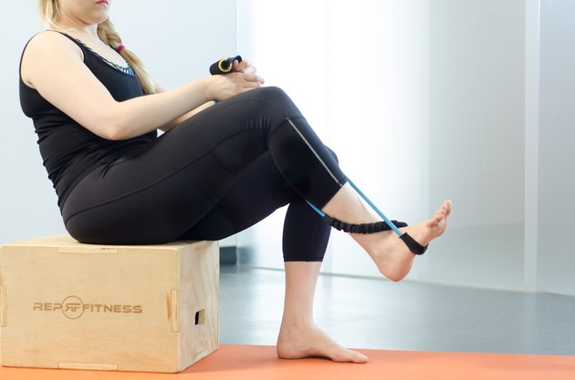 Woman performing band ankle strengthening exercise for foot pain