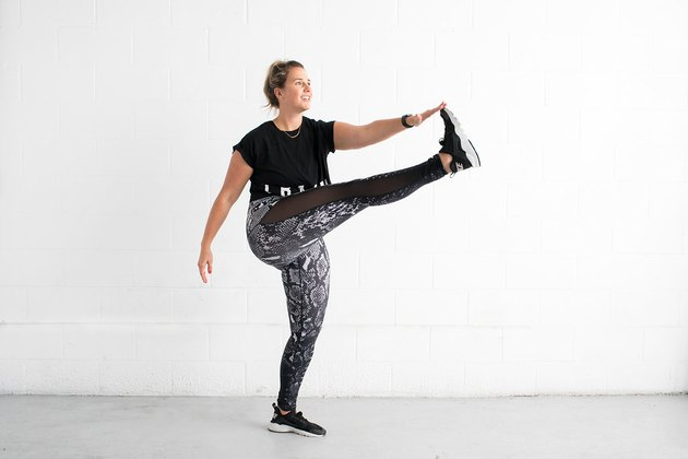 woman doing toe touch kick standing ab exercise