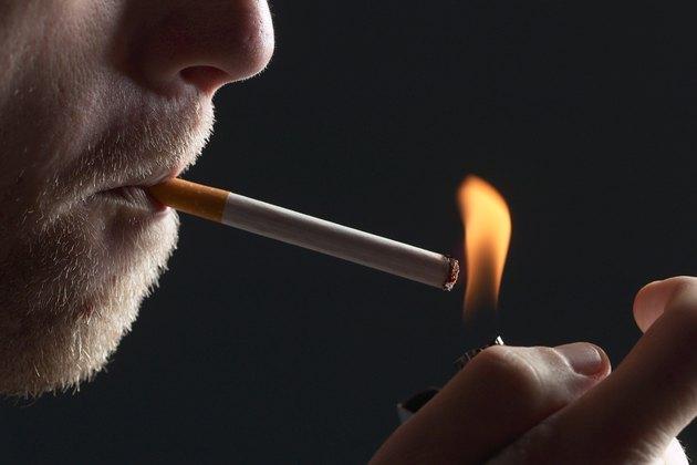 Bearded man lights cigarette.