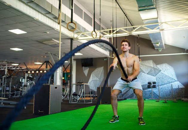 man doing battle ropes in the gym