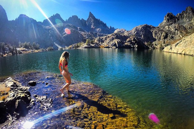 Woman walks through lake surrounded by mountain range.