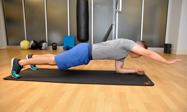 Plank position with the right arm reaching. The model is in the plank position with his right arm reaching forwards and elbow straight.