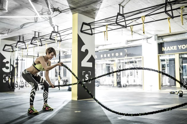 woman doing battle ropes in the gym