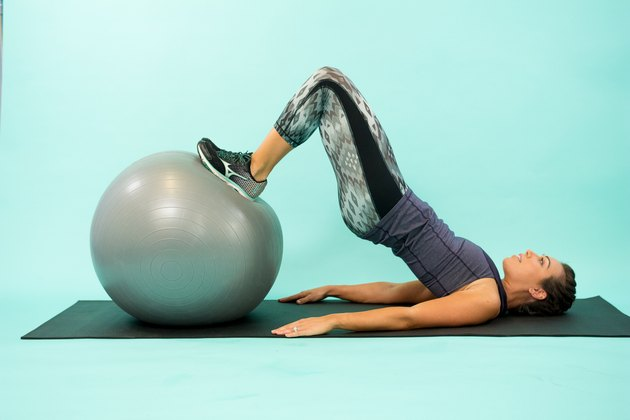 Woman performing Swiss ball hamstring curl.
