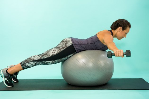 Woman performing reverse fly on a Swiss ball.