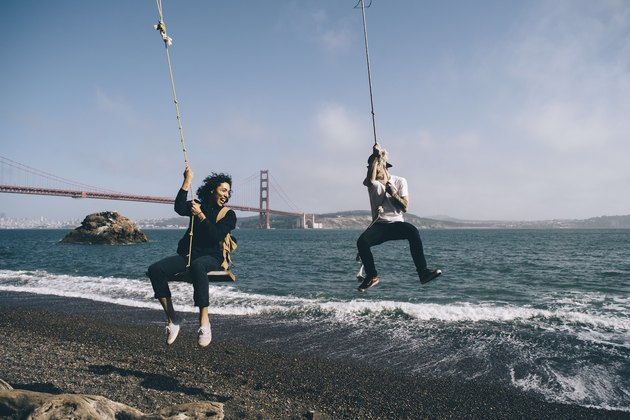 Two friends play on rope swings in San Francisco.