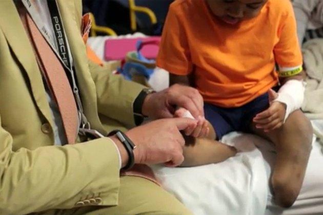 Doctor tests hands of double hand transplant recipient Zion Harvey.