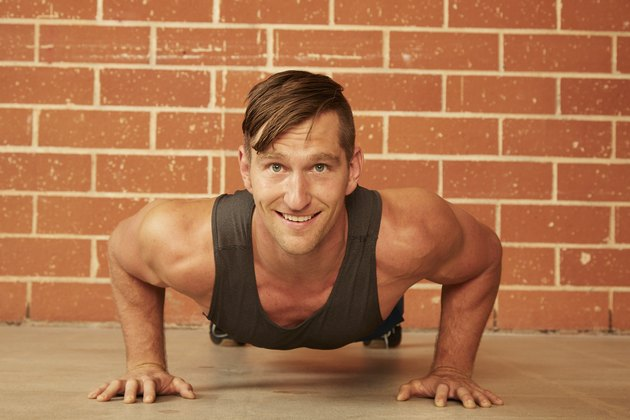 man doing a push-up variations in a gym