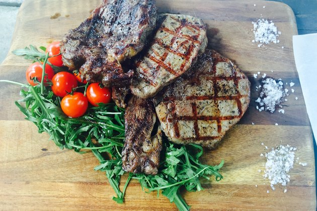 A cutting board filled with grilled steak and vegetables