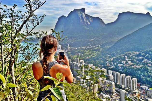 Woman takes photo of mountain and city scenery.