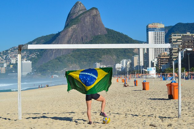 Woman doing workout on beach with Brazilian flag