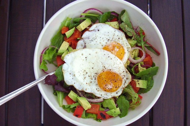 Eggs on top of a bowl of salad