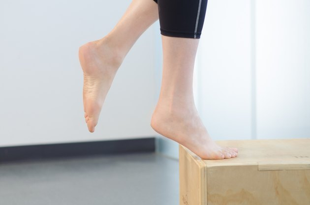 Woman performing bent-knee heel raise exercise for foot pain