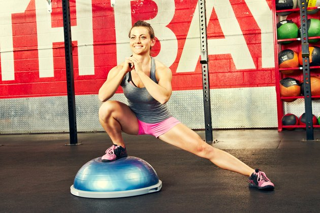 Woman performing lateral lunge BOSU ball exercise
