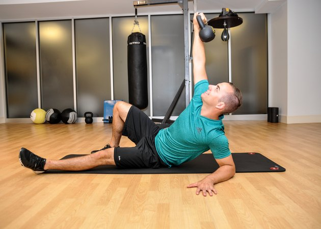 The top position of the quarter get-up. The model has his left arm on the ground, shoulders in the air, and right arm pointed up towards the sky with the kettlebell in his right hand.
