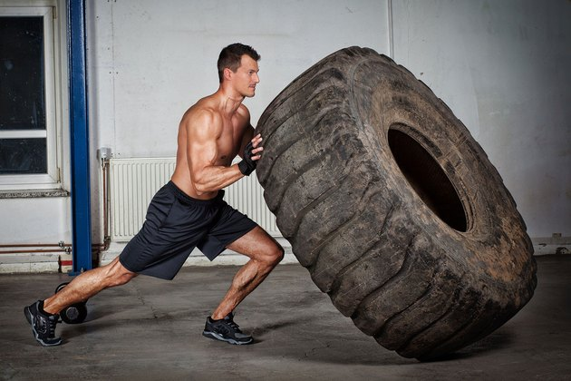 man pushing tire in crossfit gy,