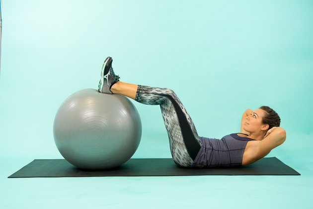 Woman performing Swiss ball reverse crunch.