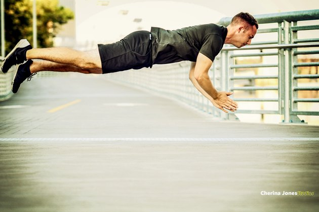Man in black shirt and black shorts performs a clap push-up while in mid-air.