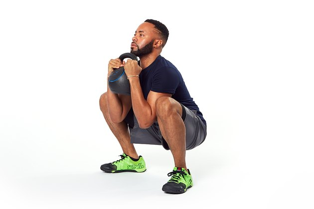 man holding a kettlebell doing a goblet squat