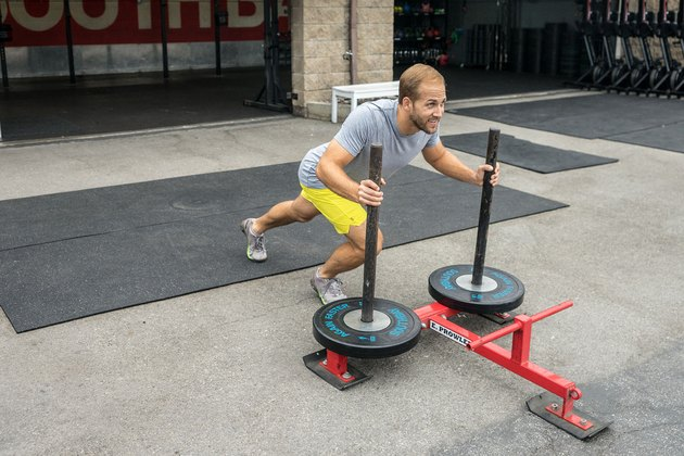 Men demonstrating sled push exercise as part of a HIIT workout for calorie burn