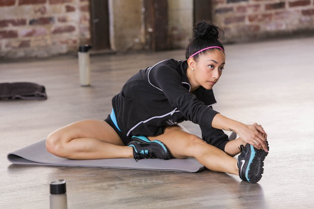 woman stretching while doing the STRONGER worokuts