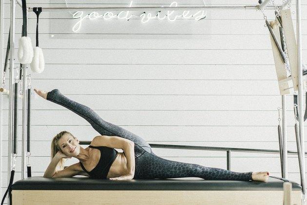 Woman performing side leg raise exercise.