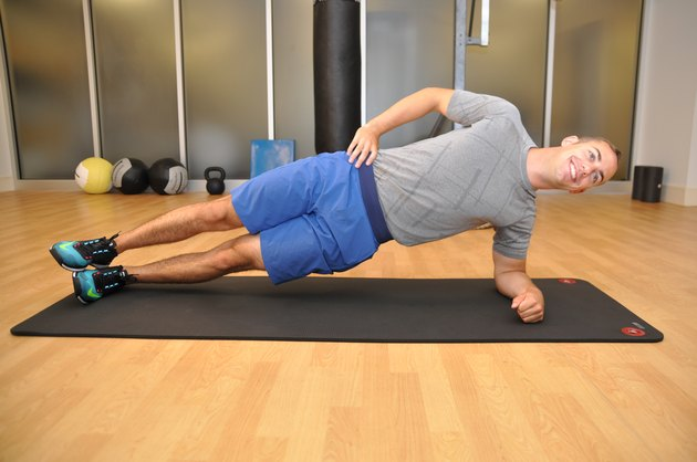 The side plank position. The model is on his left side, lying on his forearm and left foot. The model has good posture and maintains a straight line from his head to feet.