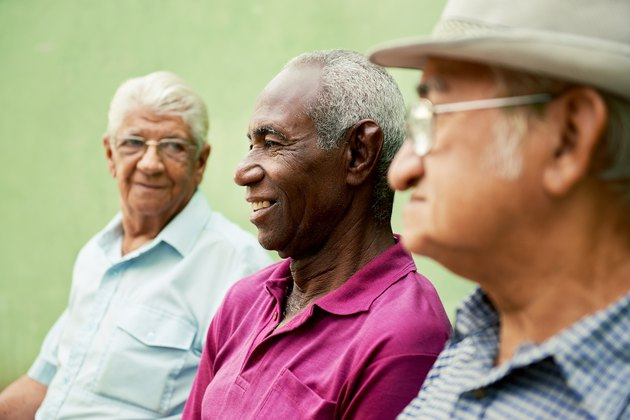 A group of elderly men chat in the park.