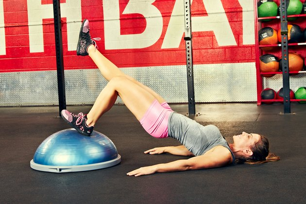 Woman performing single-leg glute bridge BOSU ball exercise
