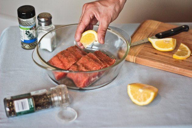 squeezing lemon on salmon