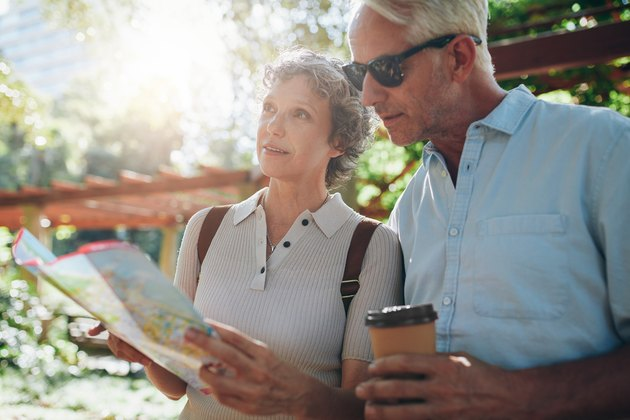 A senior couple pauses to check a map.