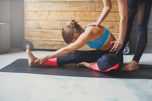personal trainer helping woman stretch