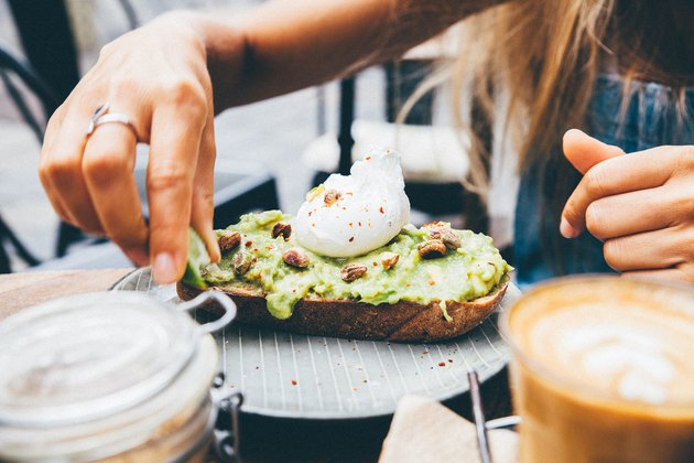 A woman eats avocado toast.