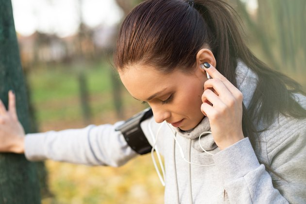 A young woman catches her breath and adjusts her headphones after a run.