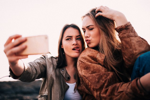 Two young women taking an usie photo.