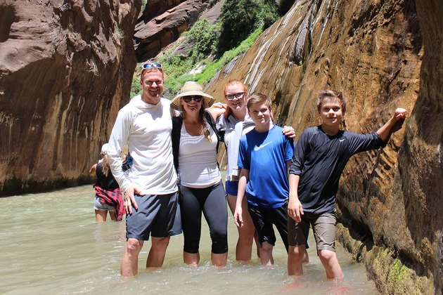 Family stands in water, surrounded by tall rock.
